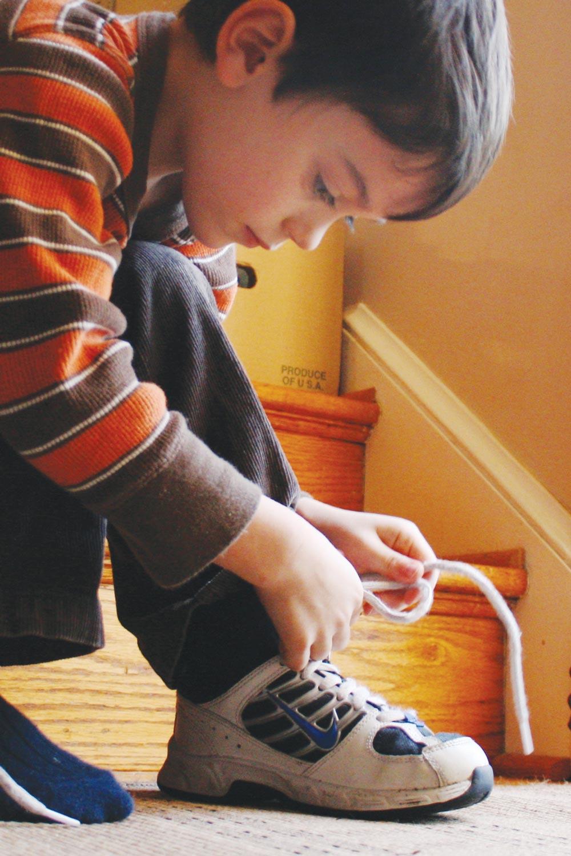 Boy Tying Girls Shoe